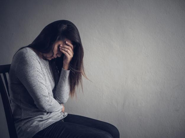 Depressed Woman sitting in a dark room.