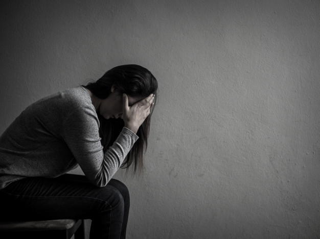 Depressed Woman sitting in a dark room. Carthage Magazine.