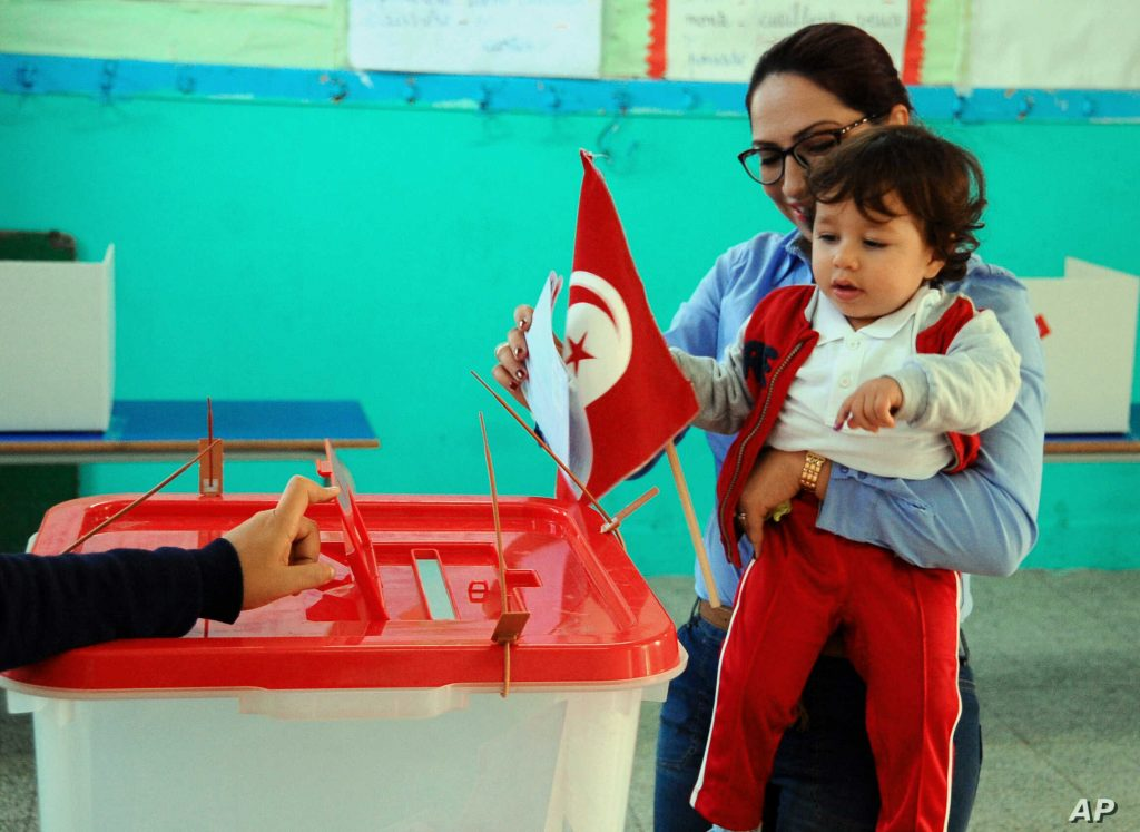 A woman casts her vote with her child, during the first round of the Tunisian presidential election, in a polling station at Marsa, Tunis, Sunday, Nov. 23, 2014. (AP Photo/Hassene Dridi)