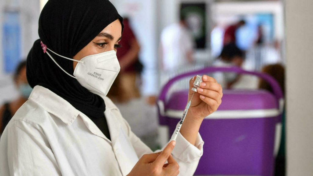 A Tunisian nurse prepares a dose of a Covid-19 vaccine at an inoculation center in Ariana governorate near the capital Tunis on August 8, 2021. © Fethi Belaid, AFP